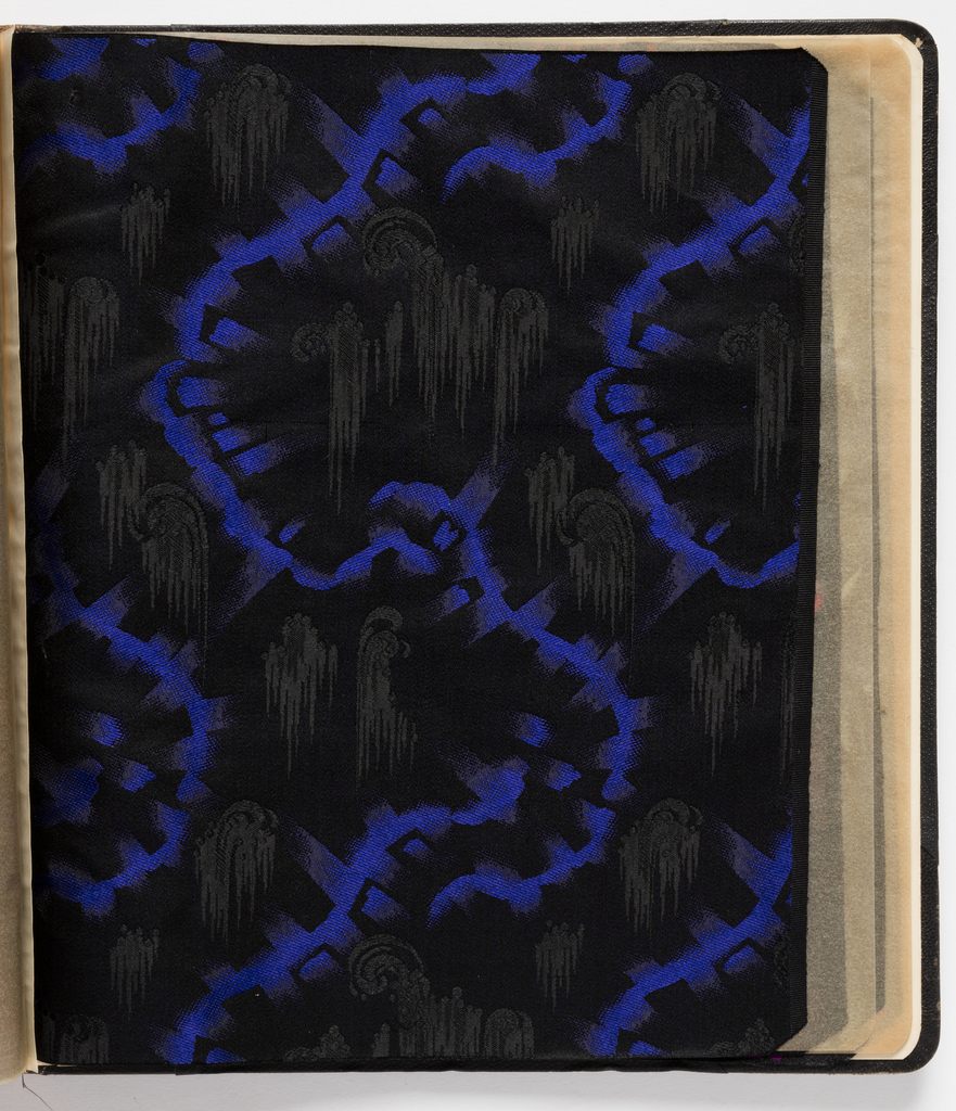 Sample book of jacquard woven silk samples, separated by transparent paper sheets, bound in leather. Samples primarily with black grounds and brilliantly colored designs.