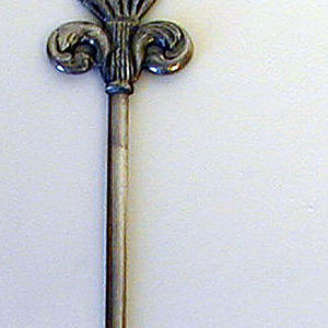 Pointed straight blade and double scroll and flower basket between acanthus leaves on terminal.