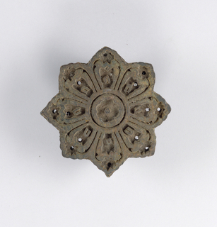 Carved block with a circular shape in the design of a stylized flower blossom with eight petals. Small holes go through block into each petal.