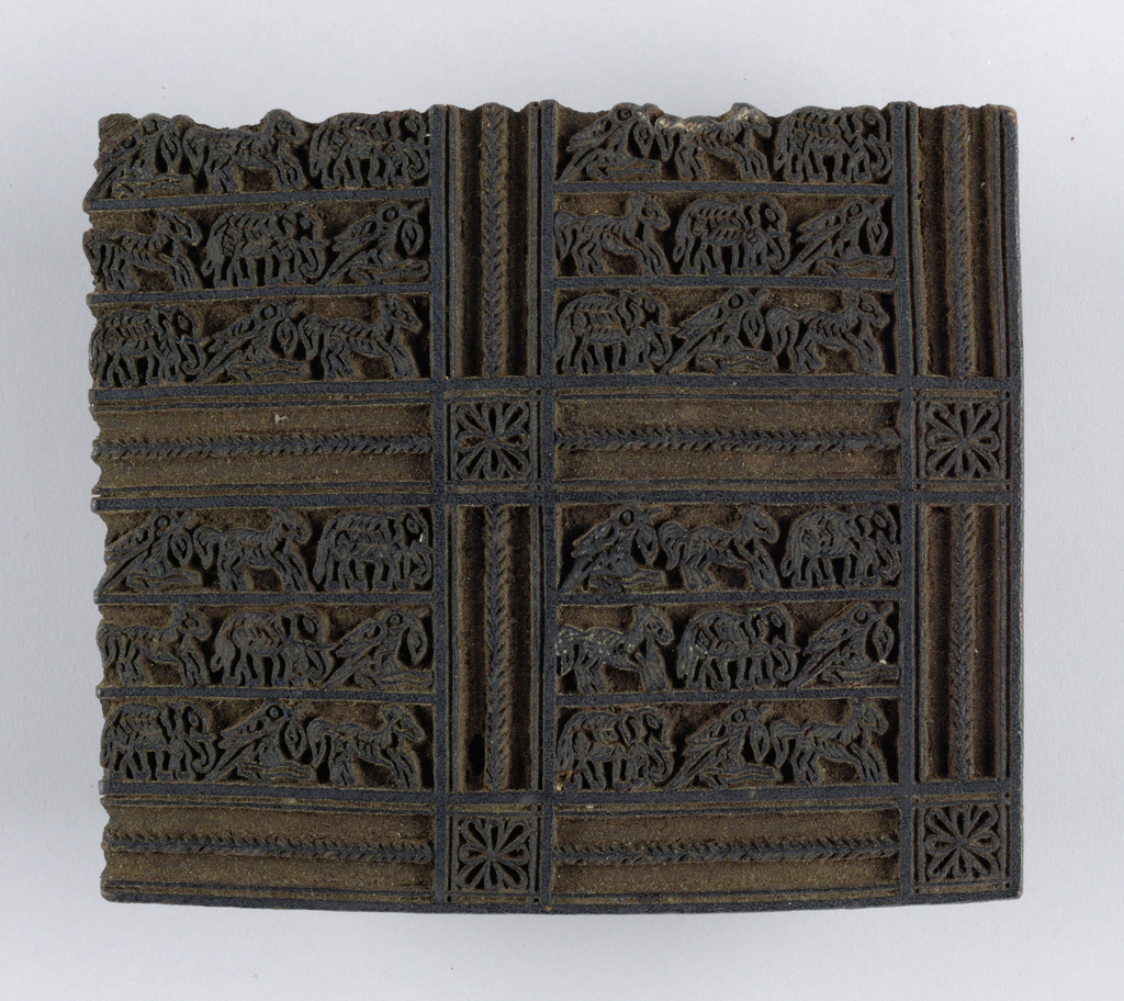Carved block design shows squares containing very small animals arranged in rows. These squares are separated by strips with little medallions at crossings. Design is in relief. Block would print one corner of the pattern.