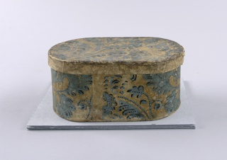 "a) Oval box covered with wallpaper. Foliate scrolls in lavender-blue with darker blue dots emphasizing the pattern in various places, on yellow ground. Margin visible at seam; b) Cover of the same as ""a"". Two joined sheets."