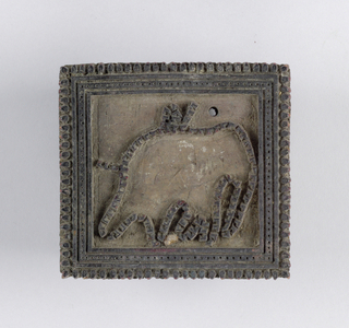 Small printing block with a design of a linear border fringed by small lozenges that enclose the outline of an elephant in relief.