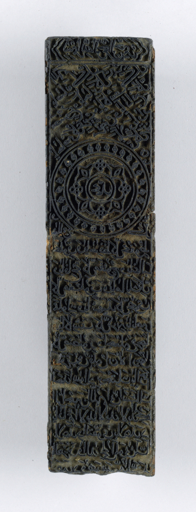 Block for printing textiles with a design of writing. Contemporary picture hangers attached.