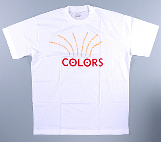 The white t-shirt is imprinted in the upper half with a floral spray design in  orange of the slogan, a magazine about the world, in English, French, German, Italian, Spanish, and Korean.  COLORS is imprinted horizontally in red in the center.