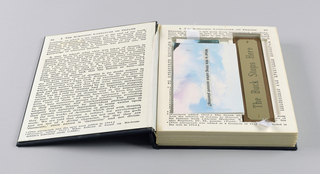 The case, exterior covered in black fabric, and labelled Effective on the spine in hand-pasted gold paper letters, is designed to simulate a book. One page within, recto, is headed Chapter I, The Scientific Literature Dealing with the Problems of Dreams, followed by text on the verso. Page three, mounted on cardboard which on the outside gives the appearance of actual pages, continues the text, but  is incised on the inside to hold two booklets, a videocassette and cover, and a desk sign. The booklets, with covers depicting sky, clouds and mountains, and blank pages within, are imprinted respectively The media is the message and What is this thing called account planning?. The videocassette shows a handwritten label, Madonna; the cover is imprinted Chiat Day Mojo case by case. The desk sign is composed of brown wood and a mounted brass plate, imprinted The Buck Stops Here.