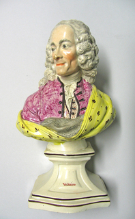 """On ivory-colored ceramic base bearing name """"Voltaire,"""" is bust of Voltaire in long powdered wig with head turned slightly to his right. He wears a rose coat open to show rose-dotted waistcoat and white cravat ends. Around the figure and covering its left shoulder is a gray-lined yellow shawl with small brown pattern."""
