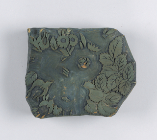 Carved block with small hole on plain side. Printing side has foliage and small flower in relief.