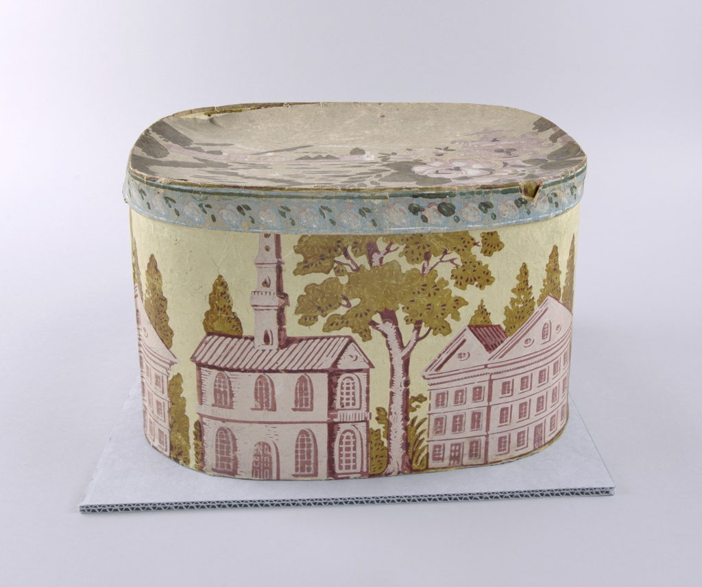 "Bandbox with pale yellow background, brownish green trees, pinky-beige brick buildings. Possibly the first capitol at Albany, with chapel called ""The Unidentified Chapel and Building"". The lid features a decorative urn with flowers. In background, temple and buildings before mountains, seen across lake with swan. Rim of lid decorated with border pattern of leaves and acorns on blue field."