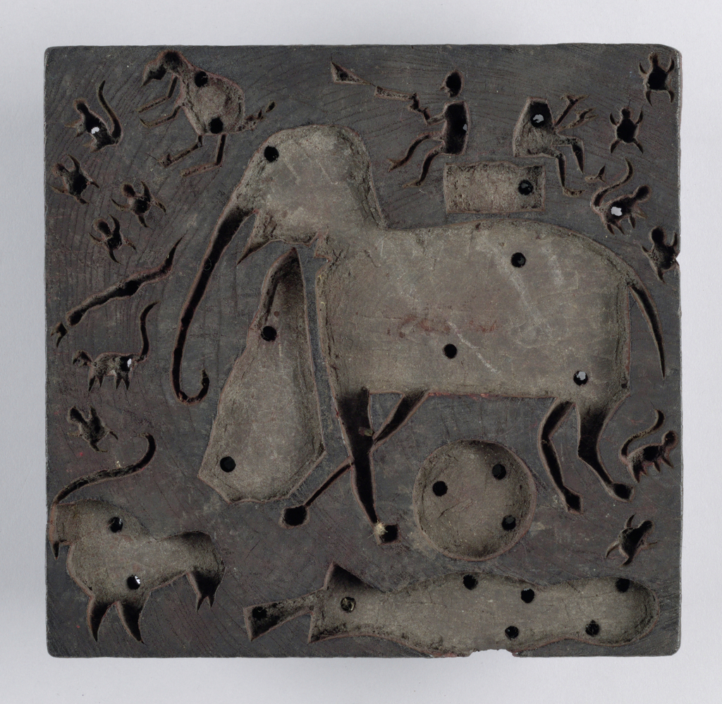 Block is carved wood in reserve design of bizarre figures. Animals float around an elephant and a sun. Two men sit on a howdah on the elephant's back. Drawing is angular and crude. Block is shot through from top to bottom with many small holes.