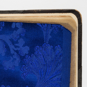 Book of jacquard woven silks, separated by transparent paper sheets, bound in leather. Samples in various colors with floral and geometric designs; many monochrome, some in two colors.