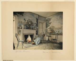 View shows an American colonial parlor with scenic wall-paper and white trim. Beside a blazing fire sits an elderly woman in colonial costume busy with her needlework.