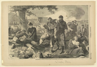 Wounded soldiers being treated by the surgeon as battle rages in the distance.