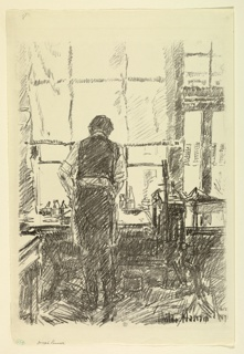 The artist is seen from the back standing at his work table before a window.