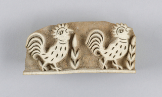 Small block for printing embroidery designs. Carved of hard wood and used to print Chickan embroidery patterns. Shows a design of two roosters in profile with plant forms in between.