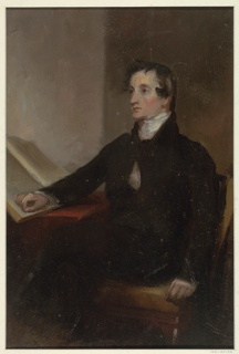 Three-quarter length portrait of a male figure, seated, turned to the left. The subject is seated in front of a reading table, his right hand resting on an open book.