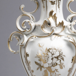 Porcelain white body with frit, glazed and gilded. (a) Tall ornate vase in two parts.  Base of outspreading scroll-work narrowing to short slender stem. Fastened by a metal bolt to ovate body which swells to shoulders embellished with handle-like leafy scrolls: body narrows to neck with rises flaring outward to irregular lip of scroll and leaf forms. White with gilded outlining of forms and nosegays and sprigs of flowers overpainted.  (b) Same as (a).  Incised marks appear under base.