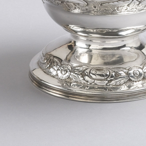 Teapot of inverted pear form repoussé and chased with rococo scrolls and flowers; applied floral finial on hinged lid.  Part of a tea set with urn and lid (b/e), creamer (c), and covered sugar bowl (d) of various dates.