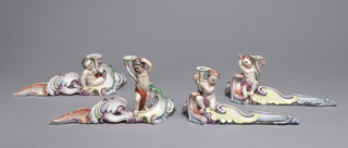 A table centerpiece formed in four sections as flowing rococo scrollwork shaded in tones of iron-red, puce, yellow, blue and green. Partially draped figures in various stances each holding a taperstick in the form of an elongated white cornucopia banded in gilding.