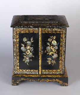 Cabinet with two doors; front painted with floral arrangements on black background, surrounded by two frames, one of gilt foliage and the other of mother-of-pearl. Top with scalloped edge and decorated with colored foliage.