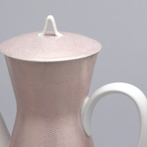 Body of roughly hour glass form; pink-glazed ground covered with tiny gilded irregular circles; large, white loop handle on one side; tall, tapering, everted white spout opposite; circular, slighlty domed pink-glazed and gilded lid with white triangular loop handle in center.