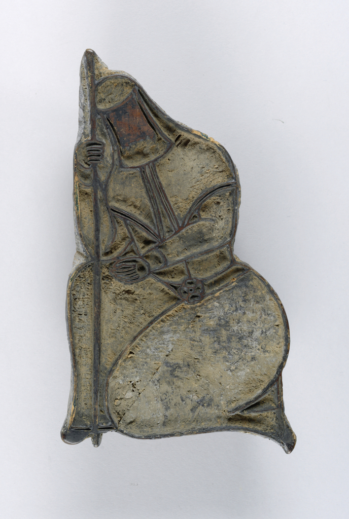 Carved woodblock with a figure of a kneeling woman.