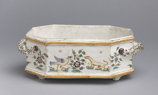 Eight-sided, horizontal form with handles, on four short feet. White ground decorated with ochre bands at rim and bottom edge. Polychrome scene of a chinoiserie figure with long lock of hair seated amidst foliage. On opposite side, a bird faces a dog. Handles are decorated with speckled blue, ochre, and green glaze, and terminate in a creature's face. White interior.