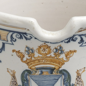 Slightly everted cylindrical form with pinched indentation at rim and two mascaron handles. White ground decorated with coat of arms surmounted by a coronet and supported by two dalmatians (leopards, ermine?) regardant; the shield is partly per saltire azure and argent, and has the star of an order suspended from the base. Swags and foliate forms below rim and above base.