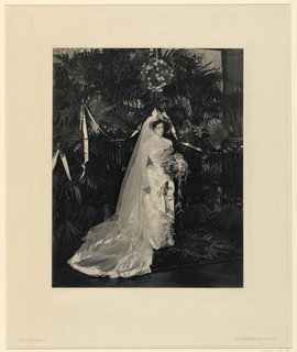 A bride, amidst foilage, with a downcast gaze holding a bouquette
