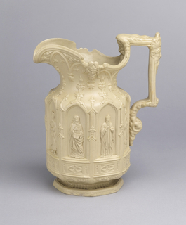 A highly decorative cream jug with detail on the body, spout and handle. The center has panels depicting figures in an outdoor scene.