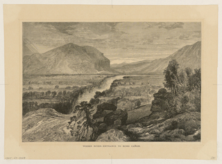 View of landscape with mountains in the distance; river running through to opening on the lower left and trees on rock formations at right.