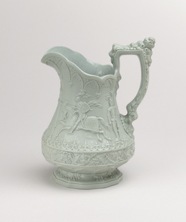 A highly decorative green jug with detail on the body, spout and handle. The center depicts a knight riding a horse in an outdoor scene.