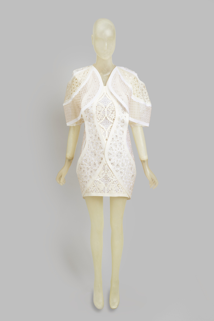 White, laser-cut lace-like dress with a overlapping layers of geometric pattern.
