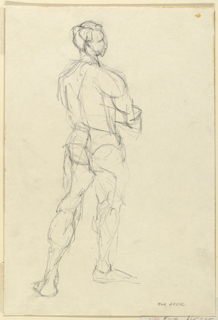 A figure of a nude male studio model seen standing from the back, his arms folded across his chest, and his gaze directed to the right.
