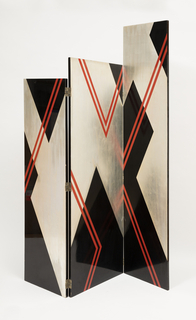 Three paneled screen. The left and right panels are attached to the center panel by hinges. Each panel is painted with an abstract zig-zag pattern in black and silver leaf, and red thin lines.