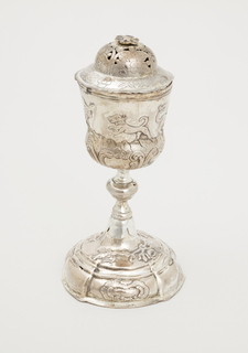 A) Waisted bowl with three fantastic animals and dog in repousse; knopped stem, scalloped where it fits over domed and stepped foot with two flying birds holding ribbons of festoons in beaks and three scrolled cartouches.   B) Domed and rimmed cover pierced and incised with floral design; finial is floral head of pin which holds round plate inside cover.