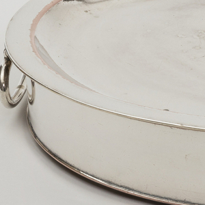 Two-part, round; with dish-shaped upper part and shallow circular lower part with straight sides; two loop handles opposite sides; diamond-shaped shield on side; interior of base and bottom of top tinned.