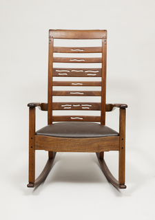 """Ladder back rocking chair with leather seat. Arms are softly rounded and apron is articulated with a """"cloud lift"""" profile. Ebony pegs and splines provide a decorative focal point, upholstered seat sets into frame."""