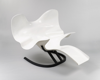 A white molded polyester chair loosely resembling an elephant on a black metal base.