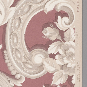 Beige and grey rococo scrolls on a maroon background on a beige ground.