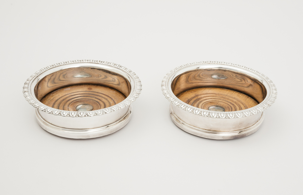 Round with low straight sides, horizontal rim top edge with egg and dart molding, stepped at base; turned wooden base with concentric grooves and central silver boss.