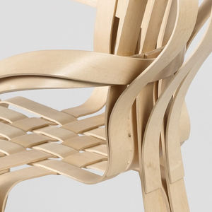 Armchair composed of strips of light-colored maple curved and glued to form back, arms, legs and seat; strips within circular seat woven to form flat surface.
