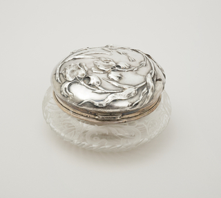 Glass bowl with curved sides, the bottom part spiral fluted, the sides engraved with leafy c-scrolls.  Mounted in silver band to which is hinged the silver repousse  cover, with two iris in high relief.  Inside gilded.