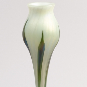 Bulbous base of gold Favrile glass, sprouting long slender clear (greenish) neck culminating in a cream-colored bud with slightly flared mouth.  Neck and bud have five slender green stems and leaves.