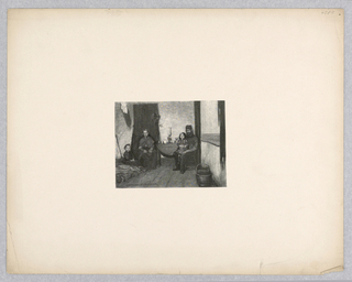 A family in an interior space faces the viewer. A man and woman sit in chairs on either side of a table, the man holding a young child while another child sits on fabric on the ground.