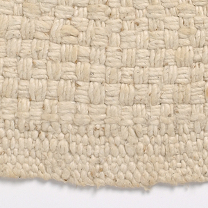 Warp and weft of loosely spun natural cotton. Variations in the weave create a caligraphic effect.