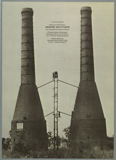 """Black and white photograph of two brick factory chimney towers.  In space at top between the towers,  black lettering in German: text announces publication of Bernd and Hilla Becher's book """"Anonymous Sculpture"""" being published by Art-Press Verlag, Düsseldorf and sold by Walther Köniq Bookshop, Cologne.  A Coca Cola sign is on the base of the left tower."""