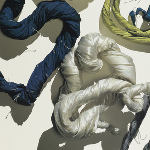 Poster features photograph of twisted fabrics arranged in a circular form.