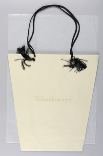 Medium-size bucket-shaped bag from series of packaging design concepts for the Japanese department store Takashimaya.  The store name is imprinted on the front and back of the bag. The atypical bag shape and the understated, yet elegant, design subtly evoke Japanese aesthetics and the attention traditionally applied to packaging.   The ends of each of two handles of woven cord thread through pair of holes on front and on back from inside, and are tied off leaving long tassles hanging on outside of bag; loose rectangular cardboard fits inside bottom of bag for reinforcement and narrow strips of cardboard are inside folded-over top of bag horizontally along long sides to reinforce handles.