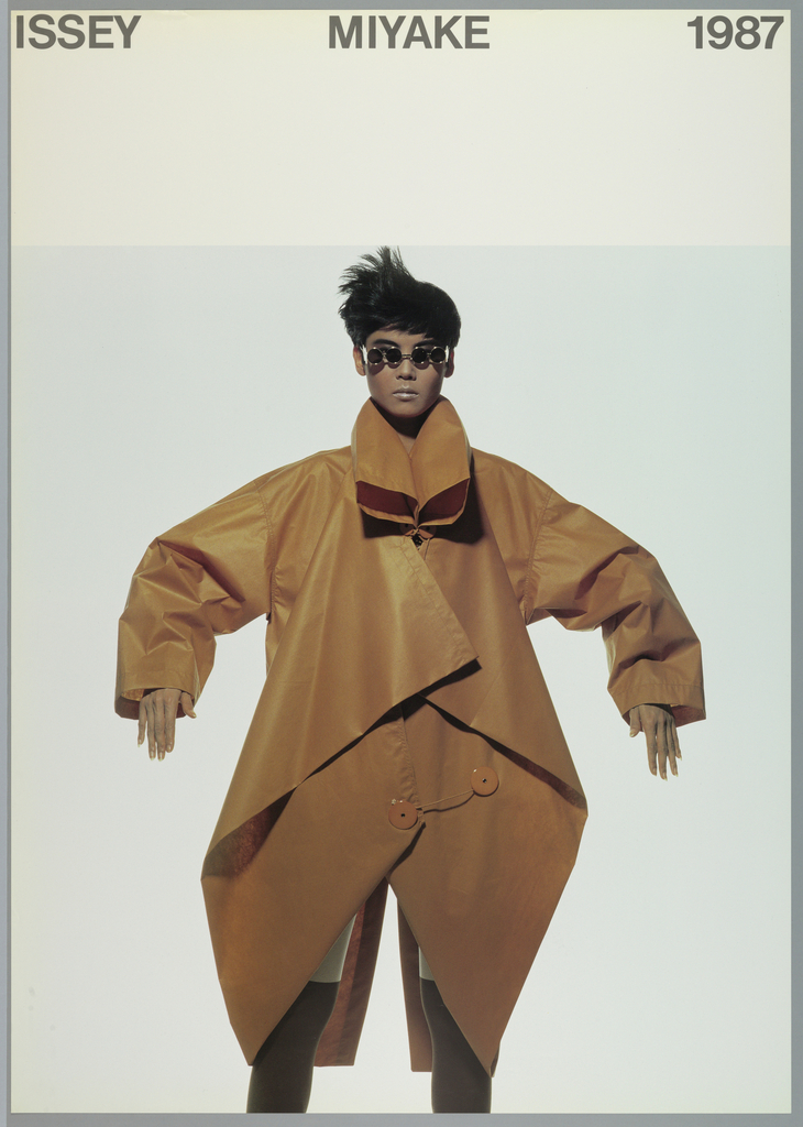 Photograph of a model with in an oversized orange jumpsuit. Above, black text in caps: ISSEY MIYAKE 1987.
