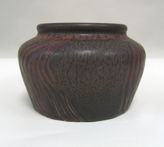 Footless bowl, tapering slightly from shoulder to base, with low neck, wide mouth, rounded lip. On cream-colored clay body, brown mat glaze ground mottled with black; four shallowly modeled flame-like forms encircling bowl mat-glazed with dark red over tan; lip and neck dark red over tan with irregular blackish-red streaking.